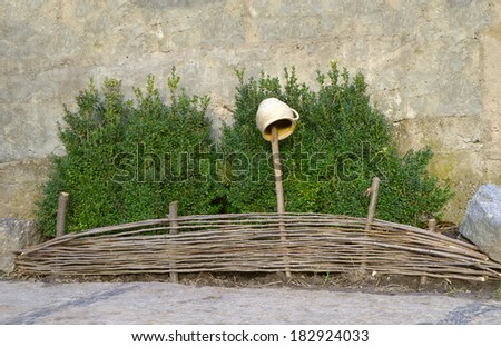 Lush green boxwood shrubs for low willow woven fence with ceramic clay vase with a handle hanging on a pole against gray stone wall background - stock photo