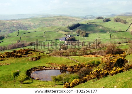 Lush green countryside and rolling hills with a remote picturesque farm in the English Lake District - stock photo