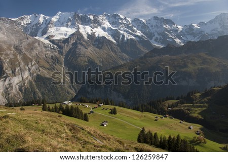 Lush green valley and village with mountains in distance - stock photo