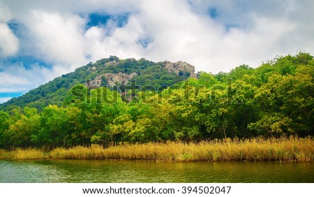 Lush green vegetation and mountain peaks covered with forests on the banks of the river Ropotamo in Bulgaria. - stock photo