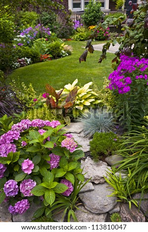 Lush landscaped garden with flowerbed and colorful plants - stock photo