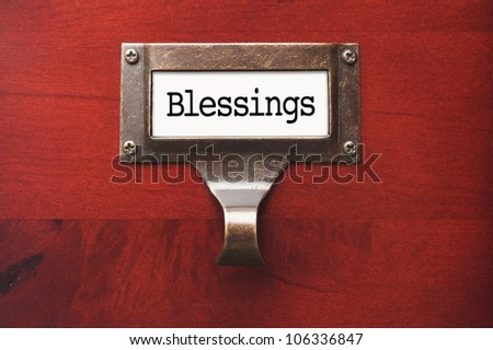 Lustrous Wooden Cabinet with Blessings File Label in Dramatic Light. - stock photo