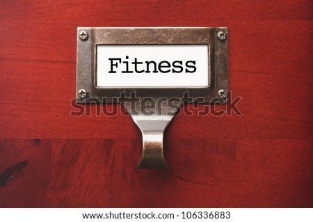Lustrous Wooden Cabinet with Fitness File Label in Dramatic Light. - stock photo