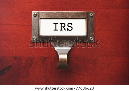 Lustrous Wooden Cabinet with I.R.S. File Label in Dramatic LIght. - stock photo