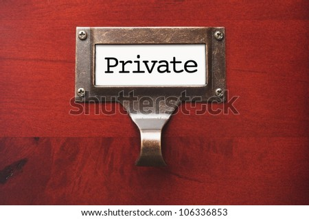 Lustrous Wooden Cabinet with Private File Label in Dramatic Light. - stock photo