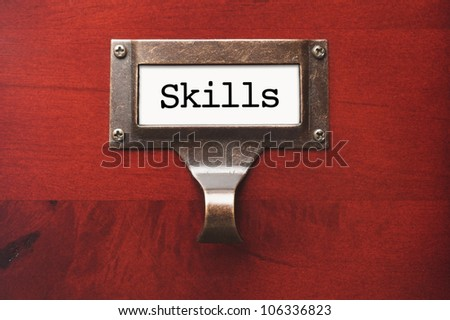 Lustrous Wooden Cabinet with Skills File Label in Dramatic Light. - stock photo