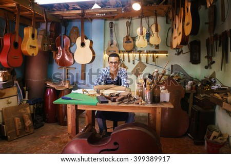 Lute maker shop and acoustic music instruments: portrait of a young adult artisan sitting at his desk and smiling at camera. He is surrounded by many guitars, mandolins and violins. - stock photo