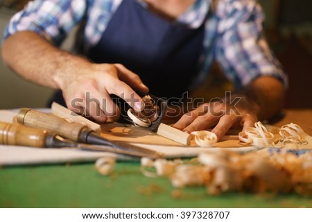 Lute maker shop and acoustic music instruments: young adult artisan cutting and chiseling wood to make a classic guitar. Closeup of his hand using a tool on guitar body - stock photo