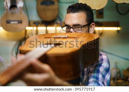 Lute maker shop and classic music instruments: young adult artisan fixing old classic guitar. The man looks carefully at bridge and arm to check the wood curvature - stock photo