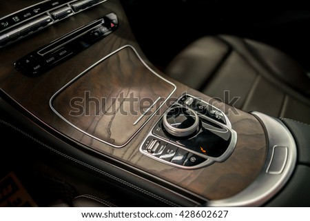 luxuly car control buttons ; Interior details Car door interior armrest with window control panel, door lock button, and mirror auto and manual control    - stock photo