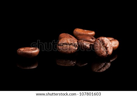 Luxurious aromatic coffee beans on black background. Luxurious coffee concept. - stock photo