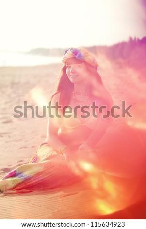 Luxurious beautiful fashionable woman on the beach at sunset - stock photo