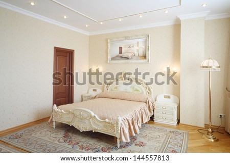 Luxurious bedroom with beautiful double bed in classic style. - stock photo