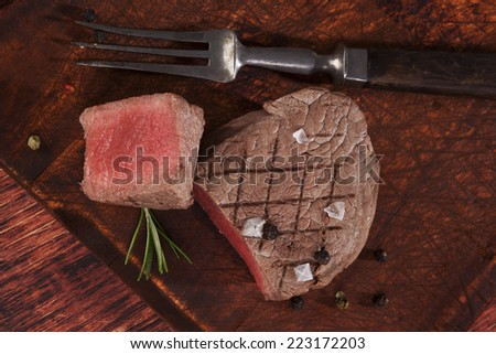 Luxurious delicious steak on wooden cutting board, top view. Culinary red meat eating.  - stock photo