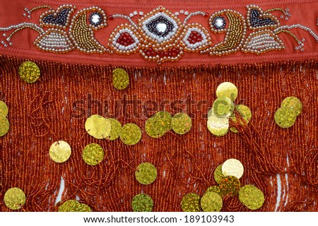 Luxurious handmade belt embroidered with red, black and silver beads and golden sequins - stock photo