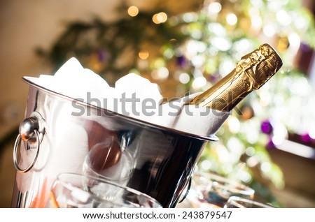 Luxurious holiday composition, a bottle of chilled champagne in an ice bucket and napkin closeup on lights background - stock photo