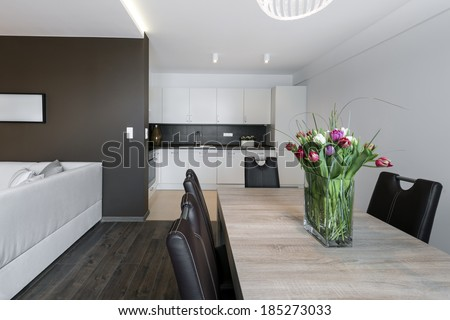 Luxurious kitchen and dinning table in modern apartment - stock photo