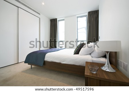 Luxurious modern bedroom with double bed, built in wardrobe and decorative bedding - stock photo