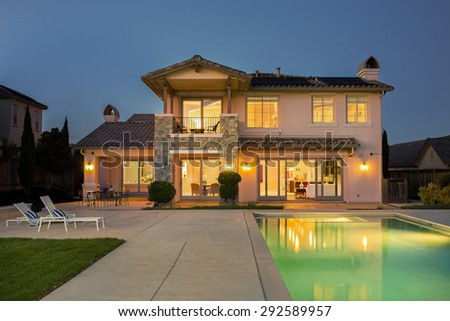 Luxurious modern house with illuminated endless pool, deckchairs at night. - stock photo