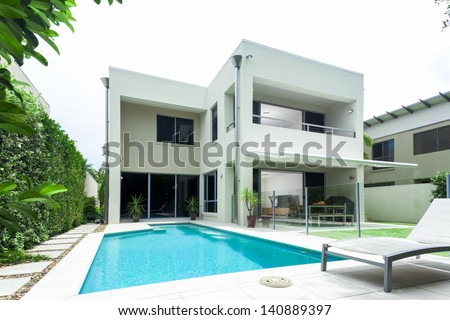 Luxurious modern house with swimming pool and backyard - stock photo