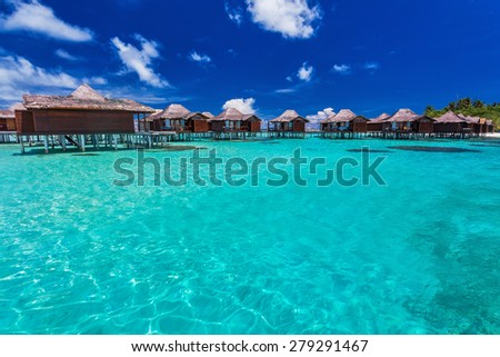 Luxurious overwater bungallows in blue lagoon on a tropical island of Maldives - stock photo