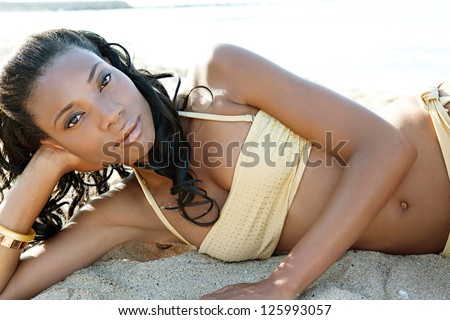 Luxurious perfect beautiful black woman laying down on a white sand beach wearing a golden bikini with shiny beads, relaxing on vacation. - stock photo