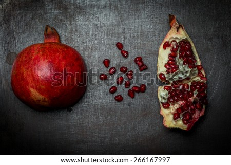 Luxurious pomegranate background. Pomegranate core on black background, top view. Healthy fruit eating. - stock photo