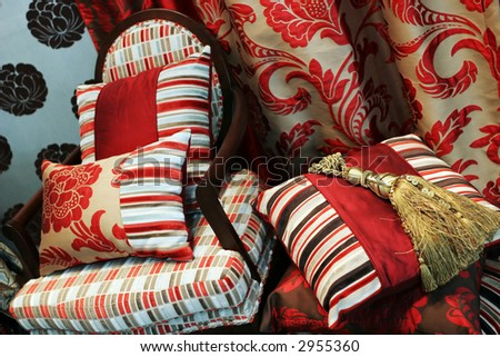 Luxurious red chair with satin pillows - home interiors - stock photo