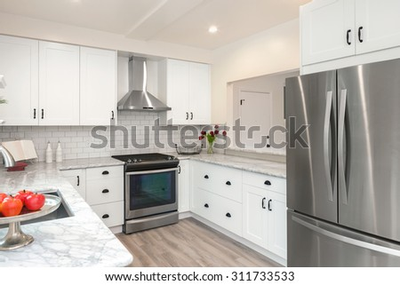 Luxurious white Kitchen in Modern Home with pearl white marble counter tops wooden floor and double door stainless steel refrigerator. - stock photo