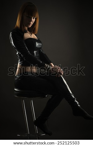 luxurious woman sitting on a bar stool - stock photo