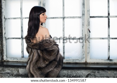 Luxurious young woman in fur coat standing by the window - stock photo