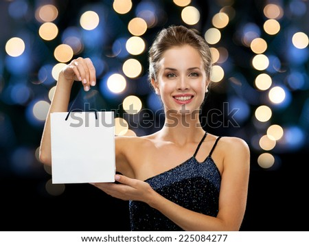 luxury, advertisement, holidays and sale concept - smiling woman with white blank shopping bag over night lights background - stock photo
