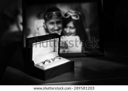 luxury amazing wedding rings in the box on the background of couple happy photograph - stock photo