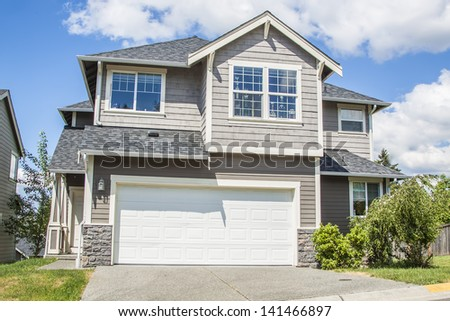 luxury American family house with landscaping on the front and blue sky on background   - stock photo