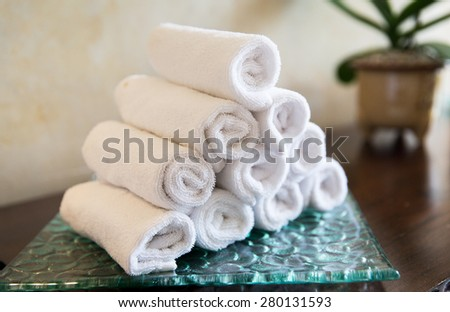 luxury and hygiene concept - rolled bath towels at hotel spa - stock photo
