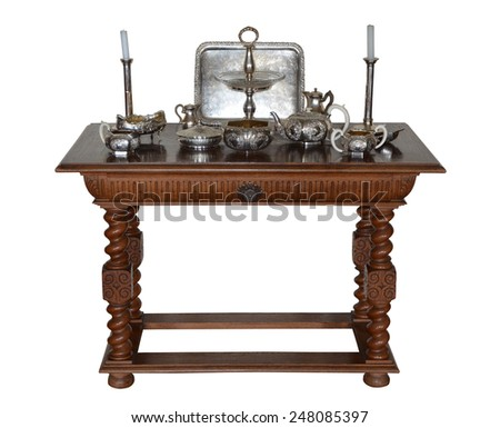 Luxury antique table for serving with silverware isolated on white background - stock photo
