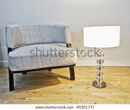 luxury armchair with a table lamp on the side - stock photo