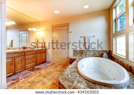 Luxury bathroom interior with tile floor. Bath tub with brown granite tile trim and vanity cabinet with large mirror. - stock photo