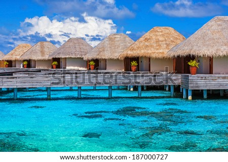Luxury beach resort on Maldives, many cute bungalows standing on transparent water, Indian ocean, romantic place for honeymoon, summer vacation concept - stock photo