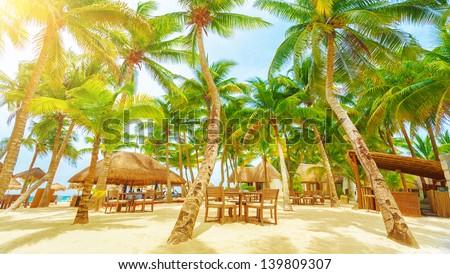 Luxury beach resort on Playa del Carmen, romantic honeymoon, beautiful bungalow on seaboard, fresh green palm tree, cozy cafe on coastland - stock photo