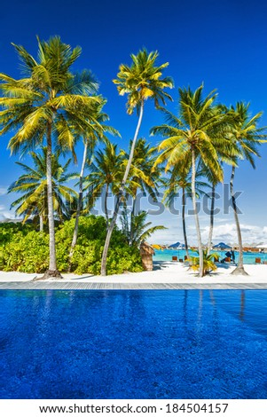 Luxury beach resort, scene destination, relaxation in paradise, exotic nature, beautiful hotel resort on an island, clear blue sea and fresh palm tree - stock photo