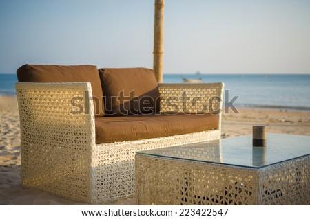 Luxury beach sofa and table on tropical island beach - stock photo