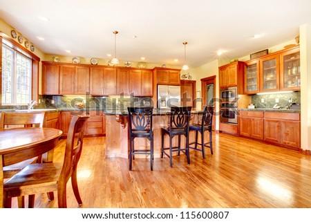 Luxury beautiful large cherry wood kitchen with green tile back splash and yellow walls. - stock photo