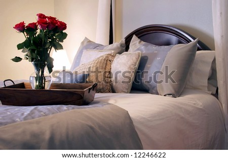 Luxury bedding with roses on a tray. Lit only by the table lamp to create warmth. - stock photo