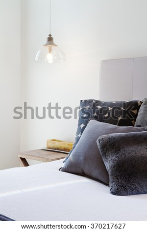 Luxury bedroom details of dark grey throw pillows and bedside pendant light - stock photo