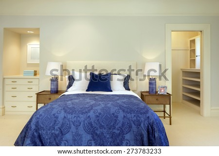 Luxury bedroom in expensive blue tones with closet and matching lamps. - stock photo