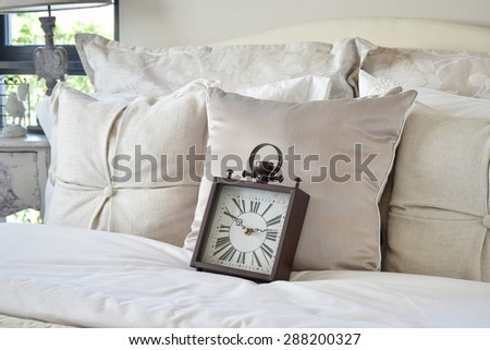 luxury bedroom interior with classic style alarm clock on bed - stock photo