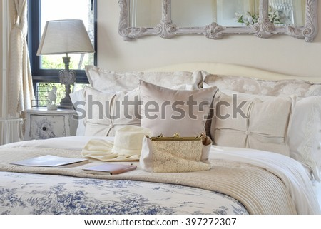 luxury bedroom interior with decorative set with vintage bag,hat,books on bed and classic style table lamp - stock photo