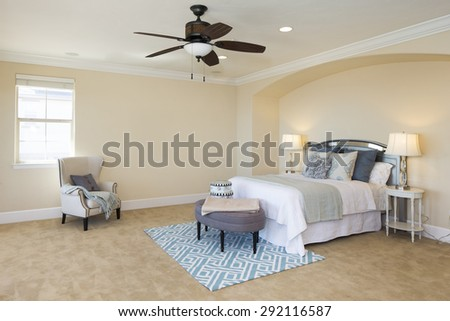 Luxury bedroom interior with rich furniture, chair and ceiling fan. - stock photo