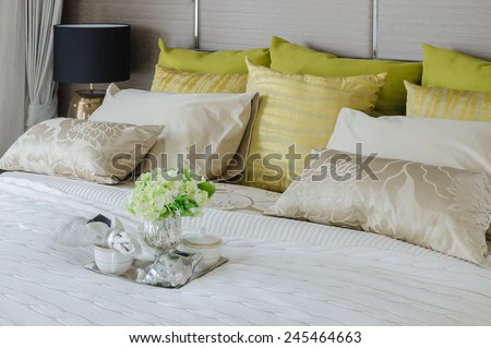 luxury bedroom with tea cup and plant in tray on bed at home - stock photo